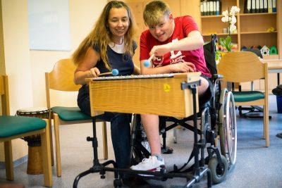 Eine Mitarbeiterin spielt mit einem Behinderten Menschen auf einem Xylophon