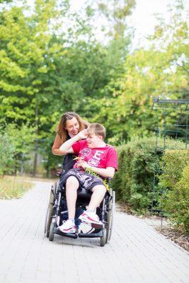 Eine Mitarbeiterin geht mit einem Rollstuhlfahrer spazieren